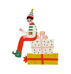 christmas elf character sitting on gift boxes vector image