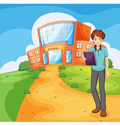 A boy holding a book standing outside the school vector image vector image