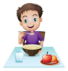 A boy eating his breakfast at the table vector image