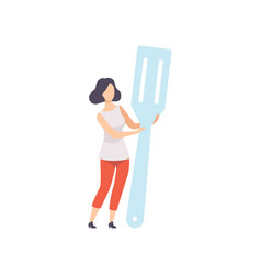 Young woman standing with a giant spatula vector