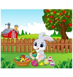 Cute Easter Bunny painting an egg in the garden vector image