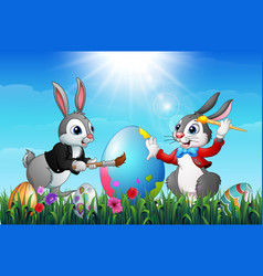 Two easter bunnies painting an eggs in a field vector