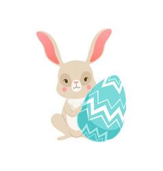 cute cartoon bunny sitting holding blue egg funny vector image