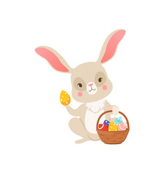 cute cartoon bunny holding basket full of colored vector image