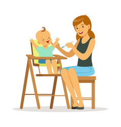 happy young mother feeding her baby in highchair vector image