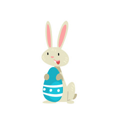 cute white easter bunny with blue colored egg vector image