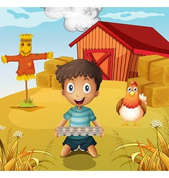 A boy holding an empty egg tray at the farm with a vector image