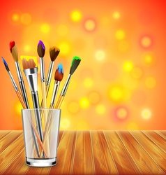 Art brushes in glass on wooden table colorful vector