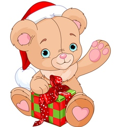 Christmas Teddy Bear holding gift vector image