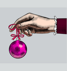 Hand of woman holding a christmas tree ball vector
