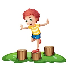 A cute young boy playing above the stumps vector