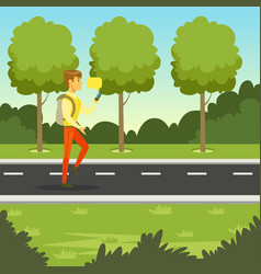young man walking in the park and using smartphone vector image