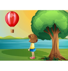 A girl watching the hot air balloon at the vector image