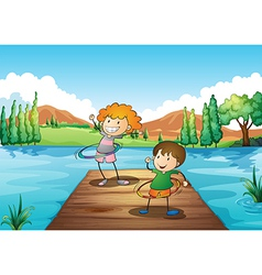 Two kids playing hulahoop at the river vector image vector image