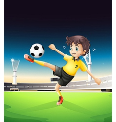 A boy in a yellow uniform playing soccer in the vector image