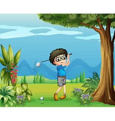 A boy playing golf near the tree vector image