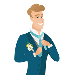 young caucasian cheerful groom adjusting tie vector image vector image