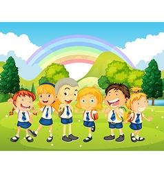 Children in uniform standing in park vector