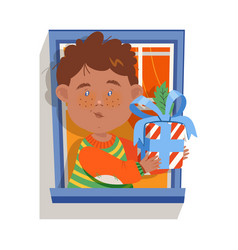 Cheerful boy in window giving wrapped gift box vector