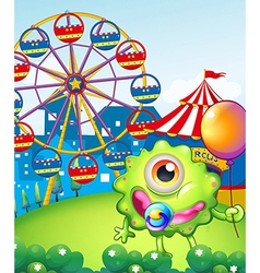 A young one-eyed monster holding a balloon near vector image