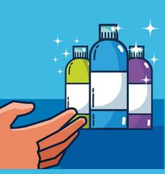 Hand grabbing detergent bottles vector