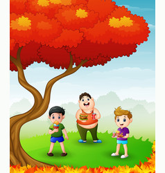happy children eating in the autumn trees vector image