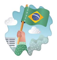 hand holding raising the national flag of brazil vector image