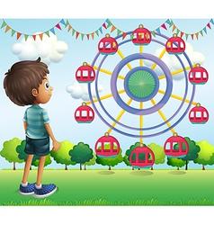 A boy watching the ferris wheels vector
