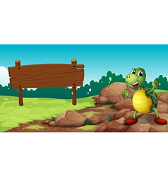 A turtle at the rocky area near an empty signboard vector image