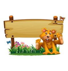 A playful bear near the empty wooden signboard vector image