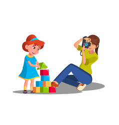 mother taking pictures of her child playing with vector image