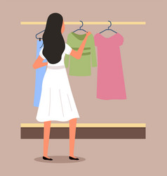 Girl chooses clothes on hanger on shopping vector