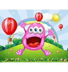 A hilltop with a very happy pink monster jumping vector