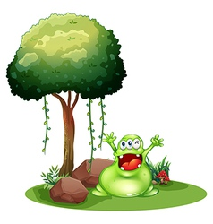 A happy monster near the tree vector