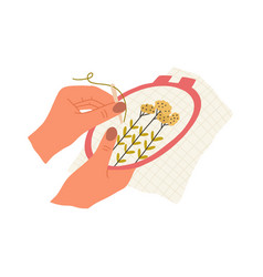 Hand with needle and thread embroidering flowers vector