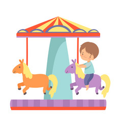 Cute little boy riding at carousel with horses vector