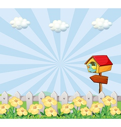 A bird at the birdhouse near the wooden fence vector image vector image