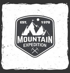 Vintage typography design with ice ax and mountain vector