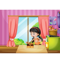 A young girl unwrapping a present inside the house vector image vector image