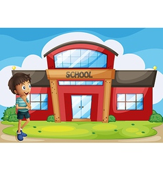 A boy in front of the school building vector image