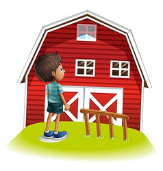 A boy standing in front of the red farmhouse vector image vector image