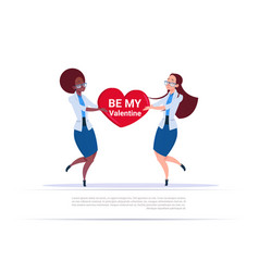 two women holding heart shape with be my valentine vector image