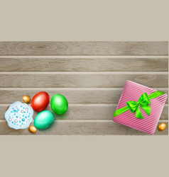 colored easter eggs cake and gift box on wooden vector image