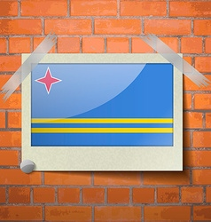 Flags Aruba scotch taped to a red brick wall vector image