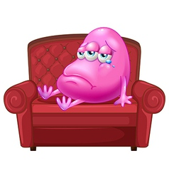 A crying monster sitting on a red sofa vector image
