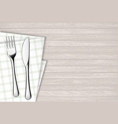 Fork and table knife on a napkin wooden table vector
