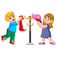Kids hanging jacket and hat on hanger stands vector