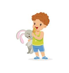 Adorable preschool boy holding bunny toy vector