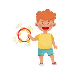 Red haired little boy playing tambourine vector