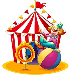 A clown sitting above a ball beside a ring of fire vector image vector image